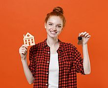 Smiling young readhead girl in casual red checkered shirt posing isolated on orange background studio portrait. People sincere emotions lifestyle concept. Mock up copy space. Hold house bunch of keys.